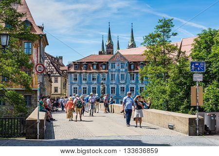 Bamberg Germany - May 22 2016: People seating and passing by bridge in downtown of Bamberg Upper Franconia Bavaria Germany.