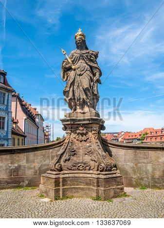 Statue of St. Cunigunde as Holy Roman Empress stands over the Regnitz river in Bamberg Bavaria Germany. Built 1750 from Johann Peter Benkert.