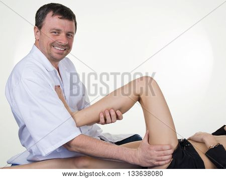 Chiropractor Massaging The Leg Of Female Patient In Physio Room.