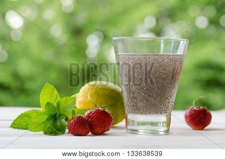 Chia Seeds Drink With Water In Transparent Glass With Lemon, Mint And Strawberry. Outdoor Photo.