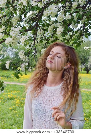 Young girl with long hair in a lyrical sensual mood stands near a flowering apple trees in the garden in spring.