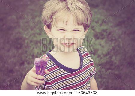Child holding a gun being tough