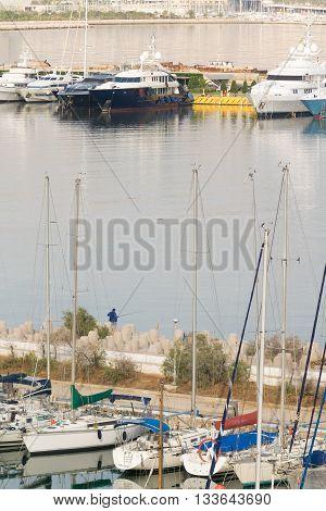 Fisherman fishes at Kastella port in Piraeus.