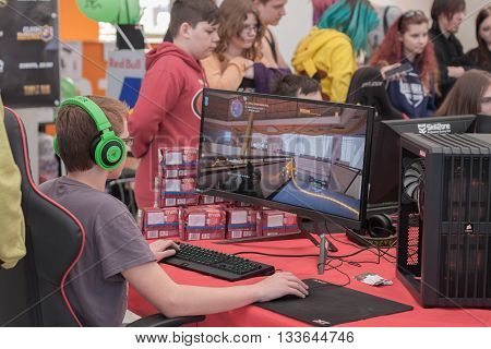 BRNO CZECH REPUBLIC - APRIL 30 2016: Young boy sits on gaming chair and plays game on PC at Animefest anime convention on April 30 2016 Brno Czech Republic