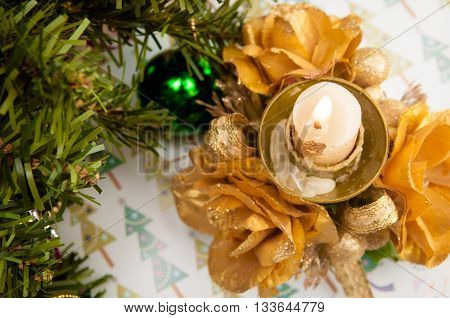 candleholder with golden roses and candle standing on a tablecloth in the winter Christmas pattern and decoration of foot Christmas tree with New Year balls