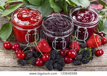 strawberry cherry and mulberry jam on a rustic table