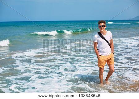 man wolking on the empty sunny beach, Crete, Greece