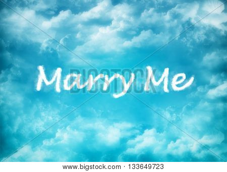 Instription Marry Me on blury cloudy background