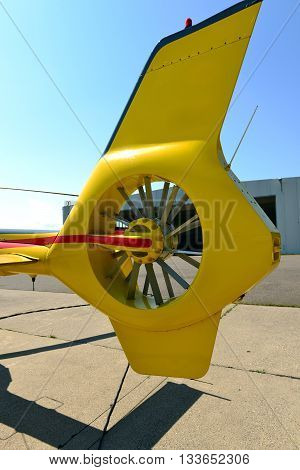 Yellow tail of helicopter with rotor inside.