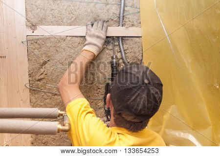 Worker driils a hole for electrical wires