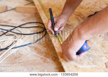Construction work. Woodwork. Male builder marking point on hardboard