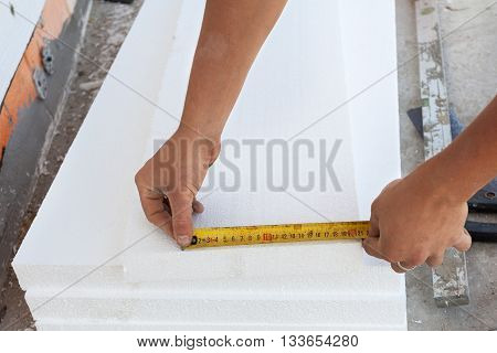Thermal insulation house foundation walls with styrofoam boards. Worker use ruller to measure the correct length of styrofoam