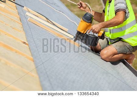 Roofer builder worker use automatic nailgun to attach roofing membrane
