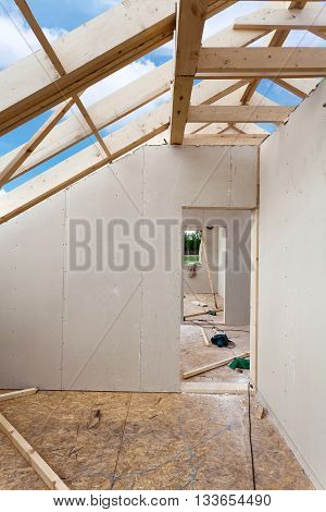 Attic room under construction with gypsum plaster boards. Roofing Construction Indoor. Wooden Roof Frame House Construction.