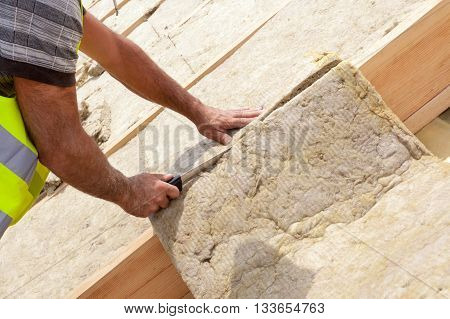 Roofer builder worker installing roof insulation material on new house under construction. Cutting rockwall with sharp knife