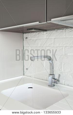 Detail of a rectangular designer kitchen sink with chrome water tap