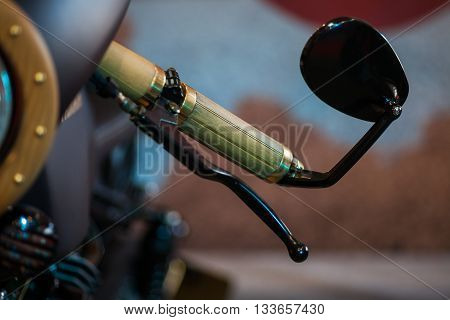 Close up shot of a motorcycle handlebar and mirror.