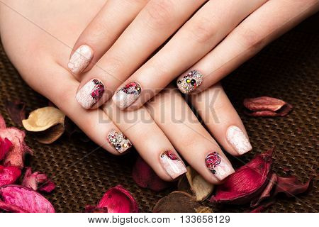beautiful manicure with flowers on female fingers. Nails design. Close-up. Picture taken in the studio on a white background.