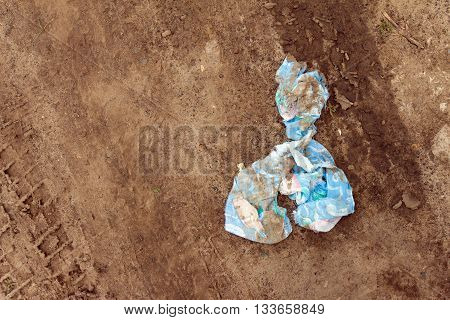 Dirty and tattered rag lying in the dirt. On the land footprint of the machine.