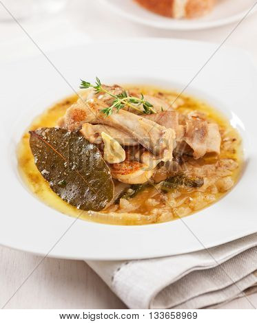 Rabbit prepared in a sauce of onions garlic and bay leaves