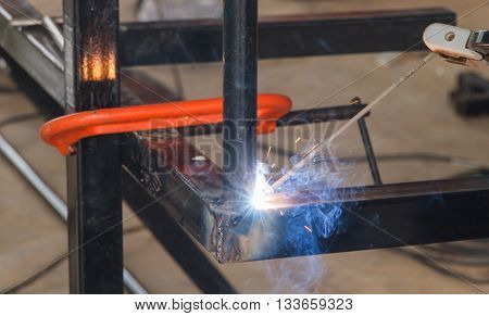 Shield metal arc welding welding and C-clamp in fabrication work shop.