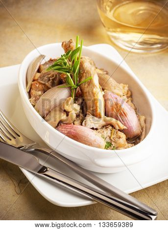 A dish of rabbit prepared with onions and mushrooms