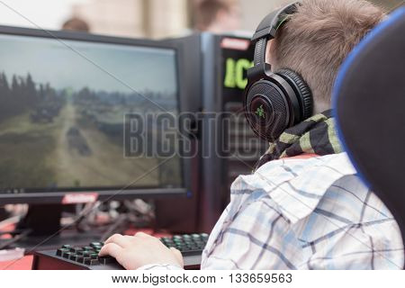 BRNO CZECH REPUBLIC - APRIL 30 2016: Young man sits on gaming chair and plays game on PC at Animefest anime convention on April 30 2016 Brno Czech Republic