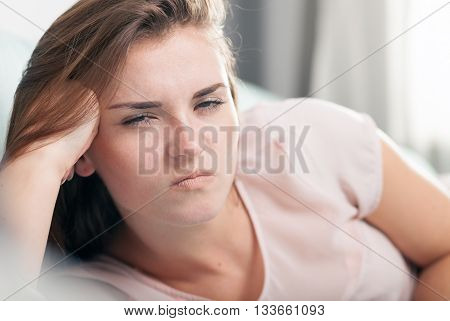 Young Woman Lying On Couch And She Is Angry. Casual Style Indoor Shoot
