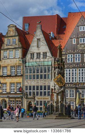 Bremen, Germany, 17th April 2016. Tourists walking and standing on the main market square with the famous statue of 'Roland of Bremen' and historic houses in the background.