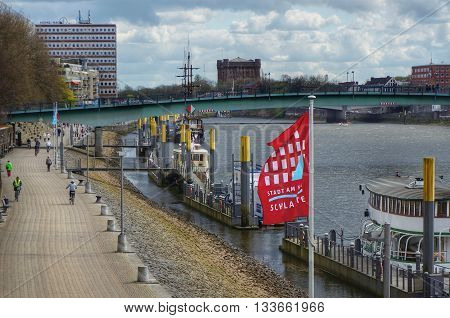 Bremen, Germany, 17th April 2016. View to river Weser. Sightseeing boats anchored at river bank. Text on flag: 'Town at River - Schlachte'. (Schlachte is the name of the city quarter).