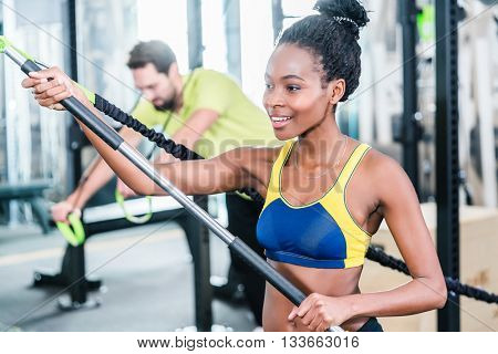 Woman and man in functional training for better fitness in sport gym
