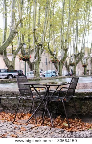 Tables and chairs of street cafes in the town square Luberon among the plane trees in the rain fall.