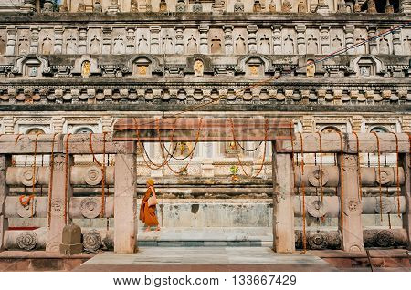 BODHGAYA, INDIA - JAN 7, 2016: Entrance arch of carved historical Budhist temple Mahabodhi and walking monk in yellow red on January 7, 2016. The temple was built in 3 century BC. UNESCO World Heritage site