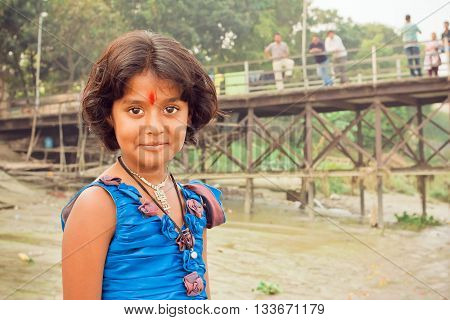 KOLKATA, INDIA - JAN 17, 2016: Unidentified girl with beautiful eyes and tilak sign playing in indian village on January 17, 2016. Kolkata's literacy rate of 87.14 perc. exceeds all-India average of 74 perc