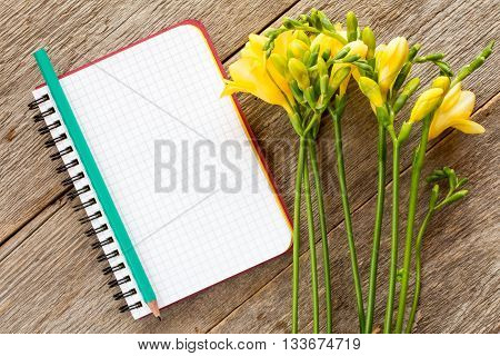 Yellow freesia flowers and blank notebook on wooden background