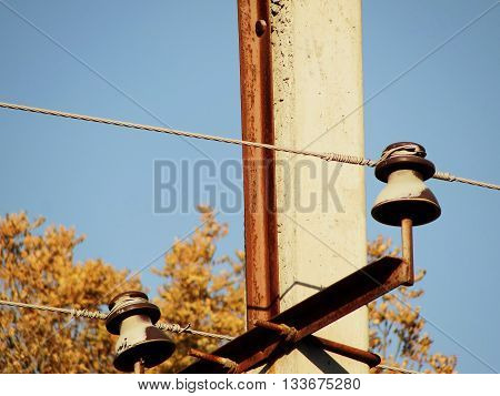 Technopark. Communication. Power line. Closeup of knot of fastening: pillar, traverse, insulator, wire.