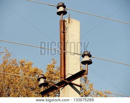 Technopark. Communication. Power line. Closeup of knot of fastening: pillar, traverse, insulator, wire.