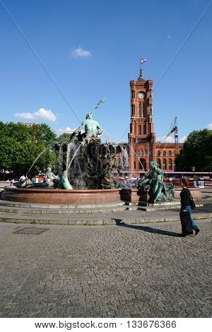 BERLIN , GERMANY - MAY 09, 2016: Neptune Fountain and Red Town Hall in Berlin. Two landmark and tourist magnets in downtown Berlin