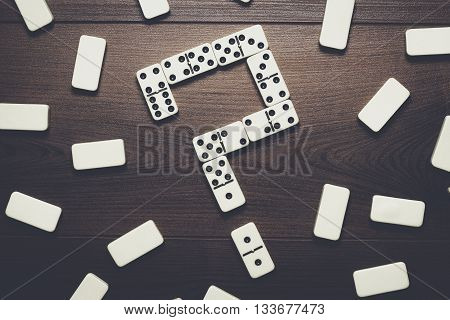 domino pieces forming question mark over wooden table