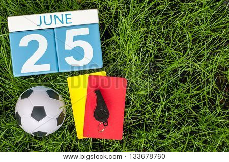 June 25th. Image of june 25 wooden color calendar on green grass background with football outfit. Summer day.