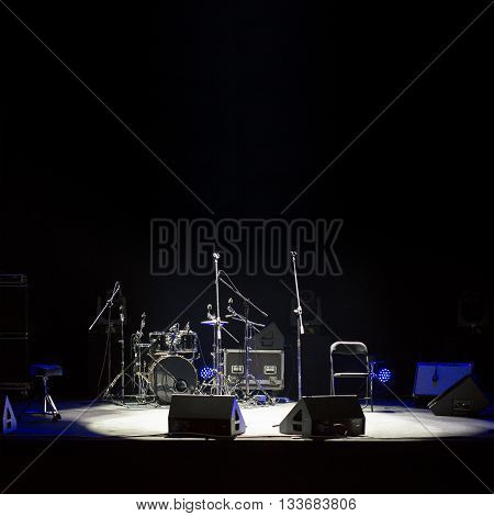 Empty stage at concert, drumkit, microphones and audio speakers