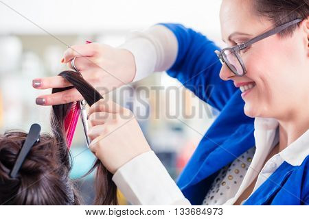 Female coiffeur divide women hair in sections with clips in shop