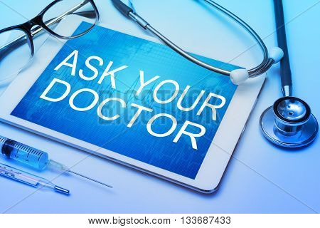 Ask your doctor word on tablet screen with medical equipment on background.