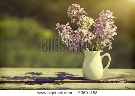 Violet flowers in a vase on a wooden table, style a vintage