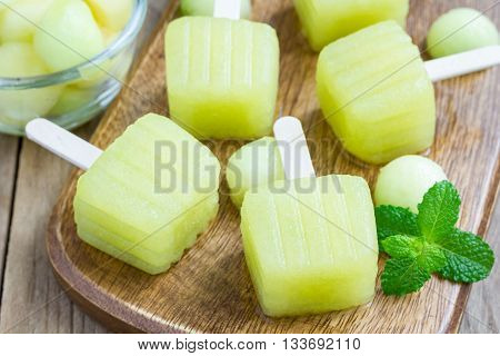 Homemade melon popsicles on a wooden background closeup