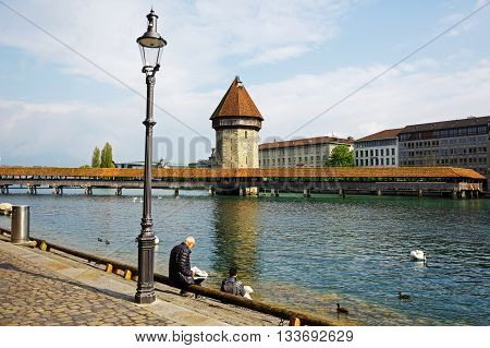LUCERNE SWITZERLAND - MAY 02 2016: Unrecognized people are sitting on the banks of the river Reuss. They can see a views of the Chapel Bridge (Kapellbruecke) with its tall tower (Wasserturm)