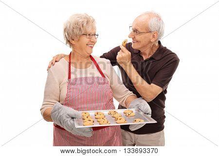Elderly couple eating homemade chocolate chip cookies isolated on white background