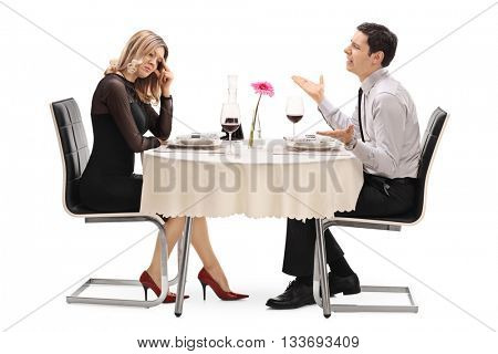 Young woman breaking up with her boyfriend seated at a restaurant table isolated on white background