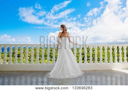 Happy bride standing next to the stone gazebo amid beautiful tropical landscape. Sea sky flowering plants and palm trees in the background. Wedding and honeymoon concept.