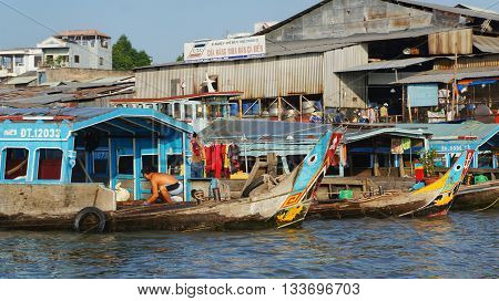 Editorial: Can Tho, Vietnam, 20th May 2016. Colorful Wooden Boats on the Mekong River, Man working on board.